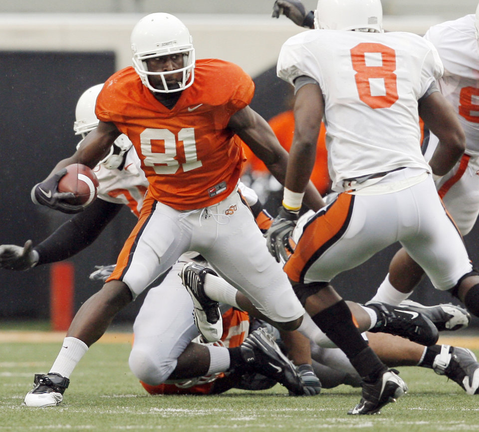 Photo - Justin Blackmon, left, moves around Daytawion Lowe on his way to a touchdown during the Orange and White spring game on Saturday.  Photo by Nate Billings, The Oklahoman