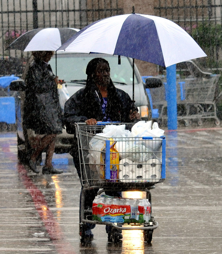 Photo - Shoppers attempt to keep dry during heavy rains on Sunday, April 6, 2014 in Ridgeland, Miss. On Sunday, street flooding plagued Jackson. Flood advisories for much of the state continued into Monday. (AP Photo/The Clarion-Ledger, Rick Guy )  NO SALES