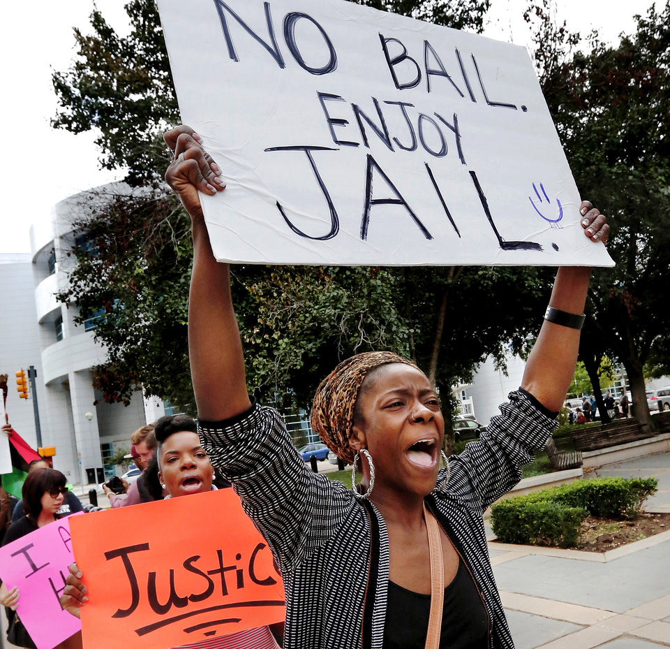 Photo - Candace Liger shouts pleas for justice while she marches. A crowd that varied in size from about a dozen to as many as 20 people at times,  marched peacefully near the Oklahoma County Courthouse Thursday morning, Oct. 2, 2014,  to protest bail for accused Oklahoma City police officer Daniel Holtzclaw.  The group called themselves OKC Artists for Justice, according to spokesperson Grace Franklin.  
