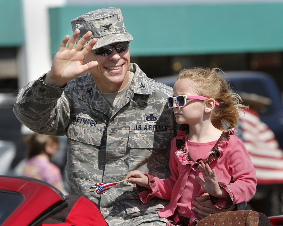 Air Force Col. Steven Bleymaier and his daughter, Caroline, 5, ride on the back seat of a convertible in the parade. Bleymaier is commander for the 72nd Air Base. Wing. He is the base commander for Tinker AFB. Del City and eastern Oklahoma County residents lined S. Sunnylane Road to show their support for America\'s military, applauding and cheering participants who marched and rode in the city\'s Armed Forces Day Parade on Saturday morning, May, 19, 2012. The parade worked its way along the Del City route for a little more than an hour. Photo by Jim Beckel, The Oklahoman
