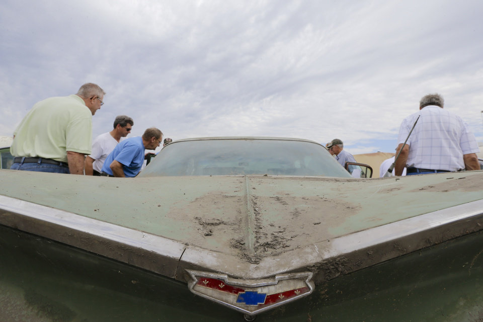 Photo - Car enthusiasts look over a 1959 Chevrolet Belair 4-door Sedan during a preview for an auction of vintage cars and trucks from the former Lambrecht Chevrolet dealership in Pierce, Neb., Friday Sept. 27, 2013. The auction takes place on Saturday and Sunday. (AP Photo/Nati Harnik)