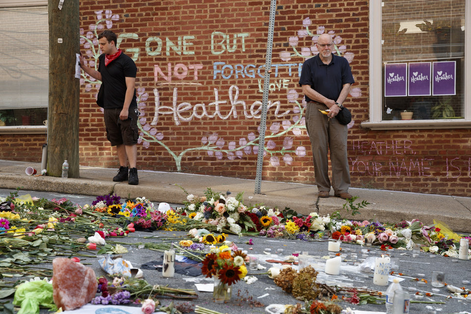Photo - Jason Charter of Washington, left, stands at the site where Heather Heyer was killed during a white nationalist rally, Wednesday, Aug. 16, 2017, in Charlottesville, Va. Charter was at the scene when a car rammed into a crowd of people protesting the rally. (AP Photo/Evan Vucci)