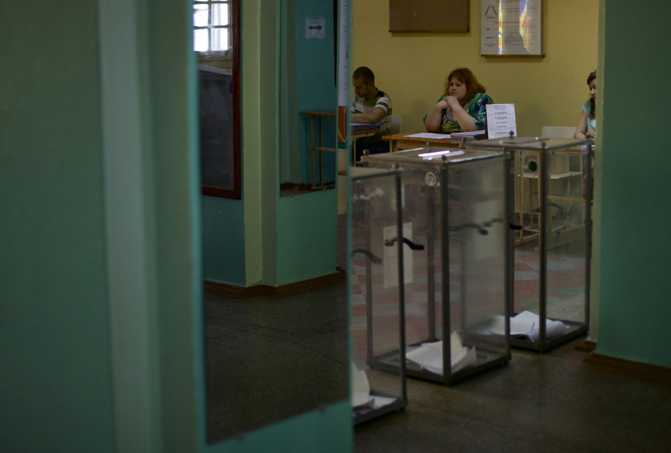Photo - Election commission officials wait for voters at a polling station in Mariupol, Ukraine, on Sunday, May 25, 2014. Ukraine's critical presidential election got underway Sunday under the wary scrutiny of a world eager for stability in a country rocked by a deadly uprising in the east. (AP Photo/Ivan Sekretarev)