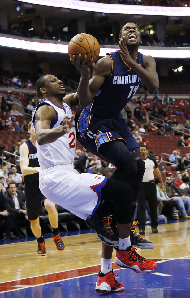 Photo - Charlotte Bobcats' Michael Kidd-Gilchrist, right, goes up for a shot after a foul by Philadelphia 76ers' Thaddeus Young during the first half of an NBA basketball game, Wednesday, April 2, 2014, in Philadelphia. (AP Photo/Matt Slocum)
