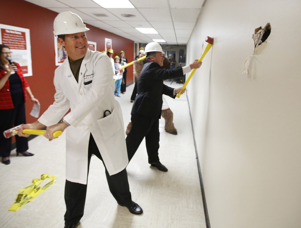 Photo - Dr. Cameron Mantor, chief medical officer for The Children's Hospital at OU Medical Center, left, and Lance Benham, a member of the advisory committee for Ronald McDonald House Charities of Oklahoma City, break down a wall with Rumble the Bison Thursday during the announcement of a second Ronald McDonald House being built in Oklahoma City.  Photo By Steve Gooch, The Oklahoman   Steve Gooch - The Oklahoman