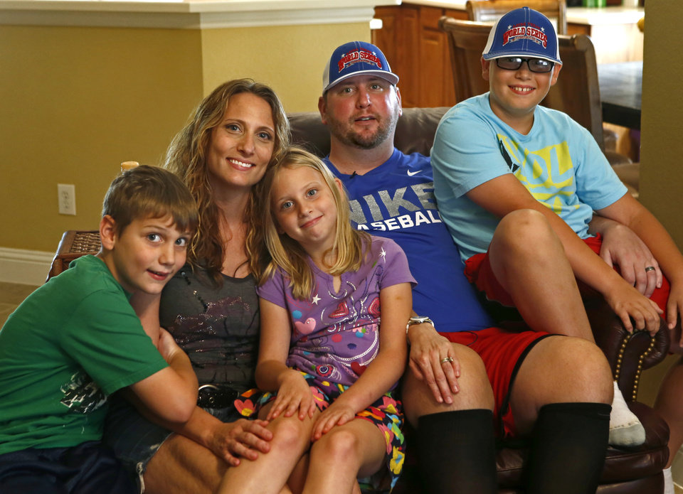 Photo - Former Tulsa hoops player J.R. Cunningham poses with, from left, son Rylan, 8, wife Angela, daughter Ashlynn, 6, and son Braedyn, 10, inside their Lantana, Texas, home.  Photo by Bryan Terry, The Oklahoman  Bryan Terry