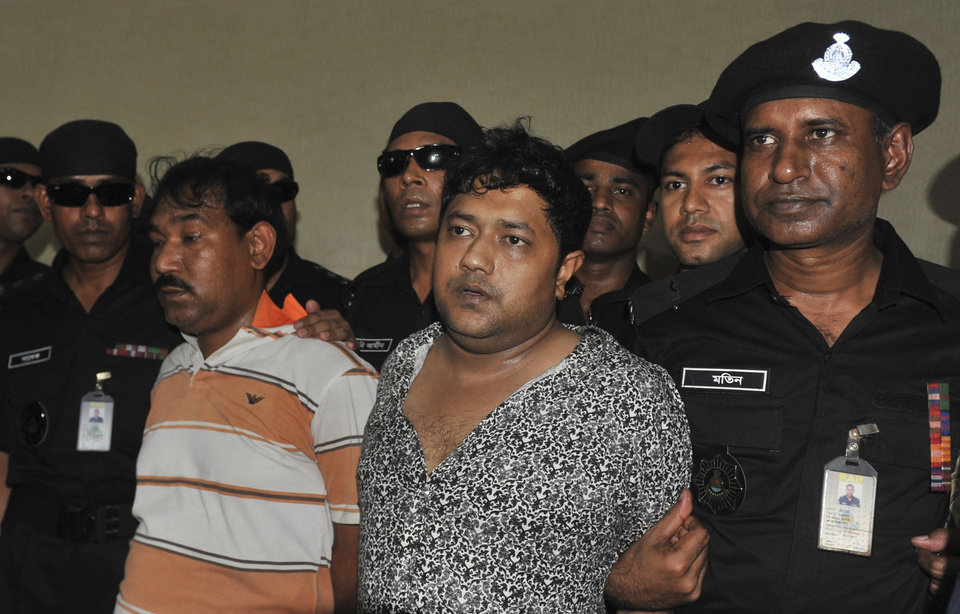 Photo - Mohammed Sohel Rana, centre right, the fugitive owner of an illegally-constructed building that collapsed last week in Bangladesh, killing some 377 people, is paraded by Rapid Action Battalion commandoes for the media along with an unidentified alleged accomplice, seen at left, in Dhaka, Bangladesh, Sunday, April 28, 2013.  Rana was arrested near the land border in Benapole in western Bangladesh, just as he was about to flee into India's West Bengal state, said Jahangir Kabir Nanak, junior minister for local government.(AP Photo)