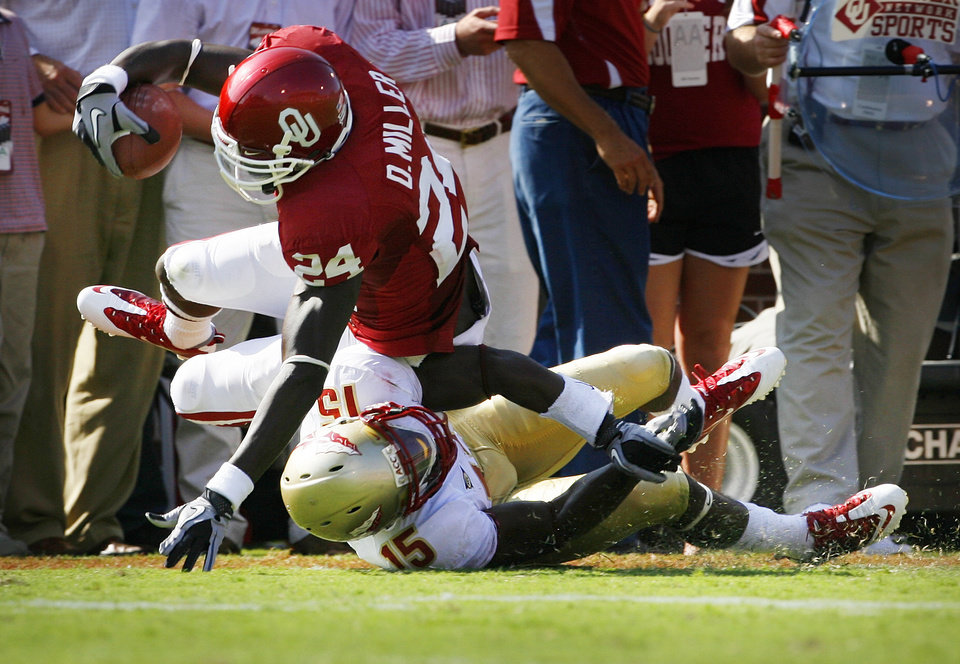 Photo - Demarco Murray (24) is tackled by Ochuko Jenije (15) during the first half of the college football game between the University of Oklahoma Sooners (OU) and Florida State University Seminoles (FSU) at the Gaylord Family-Oklahoma Memorial Stadium on Saturday, Sept. 11 2010, in Norman, Okla.   Photo by Steve Sisney, The Oklahoman