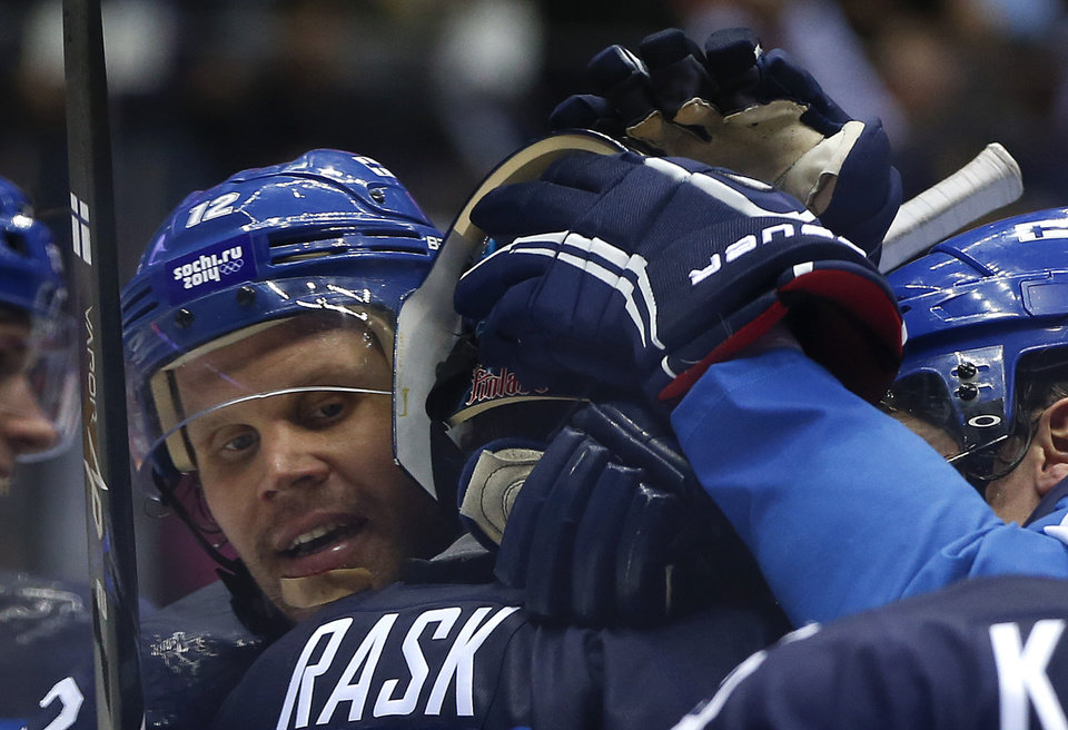 Photo - Finland forward Olli Jokinen congratulates Finland goaltender Tuukka Rask after Finland beat Russia 3-1 in a men's quarterfinal ice hockey game at the 2014 Winter Olympics, Wednesday, Feb. 19, 2014, in Sochi, Russia. (AP Photo/Julio Cortez)