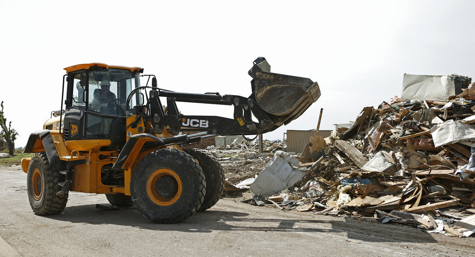 Photo - Victor Muto with Team Rubicon uses a front loader to finish demolition on a tornado-damaged house in Moore.  BRYAN TERRY - THE OKLAHOMAN