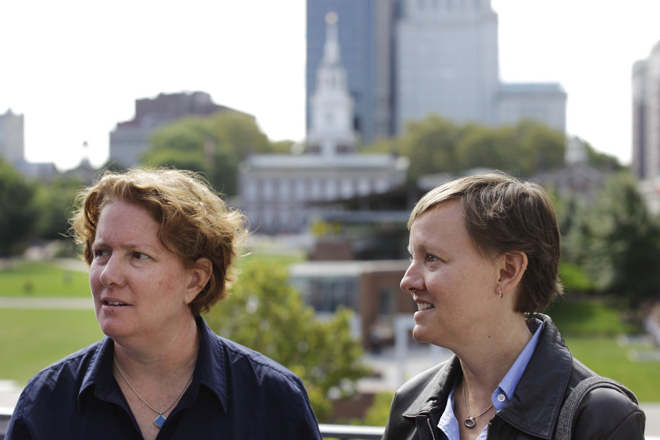 Photo - Plaintiffs Cara Palladino and her spouse Isabelle Barker speak with an attorney after a news conference, Thursday, Sept. 26, 2013, near Independence Hall in Philadelphia. Cara Palladino and Isabelle Barker, who were legally married in Massachusetts and moved to Pennsylvania, filed a federal lawsuit Thursday aiming to overturn the 1996 amendment to a state law stating same-sex marriages, including those recorded elsewhere, are not legal within the state.(AP Photo/Matt Rourke)