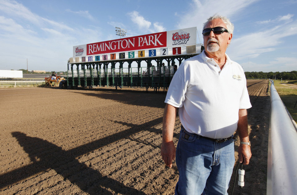 Photo - Ed Crane, starter for Remington Park, with the starters button hanging from his left hand as he watches horses run on the track during a training session at Remington Park in Oklahoma City Wednesday, Aug. 28, 2013. Remington opened 25 years ago and Ed has worked there all 25 years. Photo by Paul B. Southerland, The Oklahoman  PAUL B. SOUTHERLAND - PAUL B. SOUTHERLAND