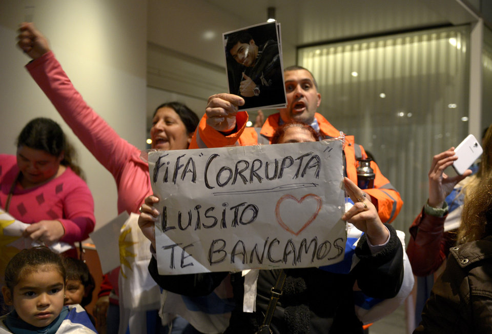 Photo - Fans of Uruguay's national soccer team await the arrival of Uruguay's player Luis Suarez with a sign that reads in Spanish