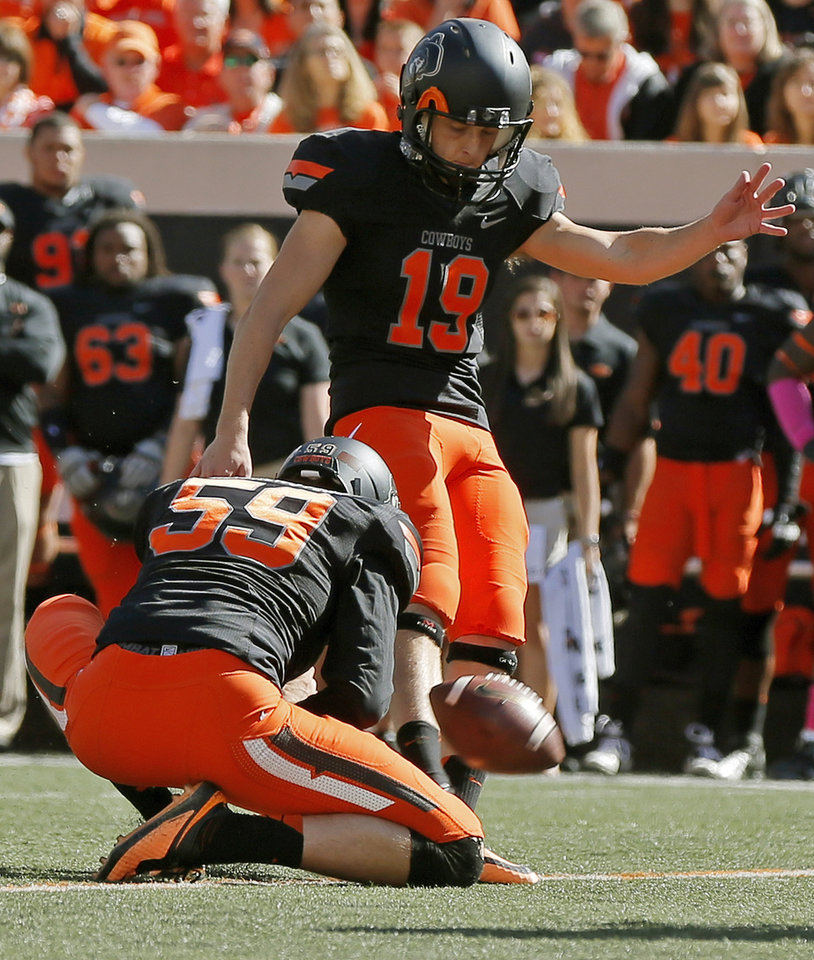 Oklahoma State's Ben Grogan (19) kicks a 30-yard field goal as Michael Reichenstein (59) holds in the second quarter during a college football game between the Oklahoma State University Cowboys (OSU) and the Kansas State University Wildcats (KSU) at Boone Pickens Stadium in Stillwater, Okla., Saturday, Oct. 5, 2013. Photo by Nate Billings, The Oklahoman