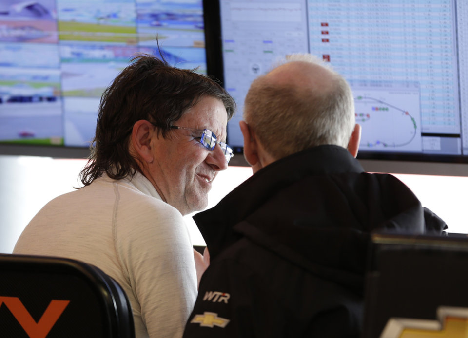 Photo - Car owner and driver Wayne Taylor, left, talks with a crew member in his pit stall during the IMSA Series Rolex 24 hour auto race at Daytona International Speedway in Daytona Beach, Fla., Sunday, Jan. 26, 2014.(AP Photo/John Raoux)
