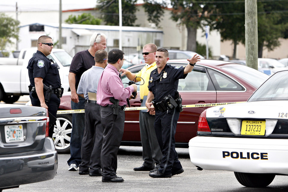 Photo -   Officers invesitage the scene where Anthony Giancola's car is surrounded in caution tape in Lealman, Fla., Friday, June 22, 2012. Authorities said Giancola, an ex-Tampa Bay-area middle school principal who lost his job over a drug arrest five years ago, went on a rampage Friday, stabbing several people, killing at least two. Authorities said there were 11 victims in all, and several are being treated at area hospitals for injuries ranging from minor to life-threatening. (AP Photo/Tampa Bay Times, Melissa Lyttle) TAMPA OUT; CITRUS COUNTY OUT; PORT CHARLOTTE OUT; BROOKSVILLE HERNANDO TODAY OUT