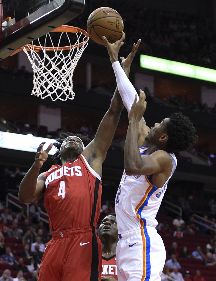Photo - Oklahoma City Thunder guard Shai Gilgeous-Alexander, right, shoots as Houston Rockets forward Danuel House Jr. defends during the first half of an NBA basketball game, Monday, Oct. 28, 2019, in Houston. (AP Photo/Eric Christian Smith)