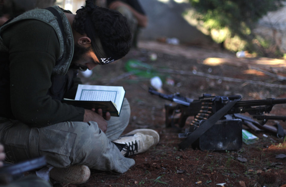 Photo - In this Thursday, Nov. 15, 2012 file photo, a Syrian rebel reads Quran during clashes with government forces in Aleppo, Syria. Through mid-2012, rebel power grew and Assad's army ramped up its response. Relentless government shelling leveled neighborhoods and killed hundreds. Regular reports emerged of mass killings by the regime or thugs loyal to it, pushing more Syrians toward armed struggle. The government, which considers the opposition terrorist gangs backed by foreign powers, denied any role, and does not respond to requests for comment on its military. The rebels, too, were accused of atrocities. (AP Photo/ Khalil Hamra, File)