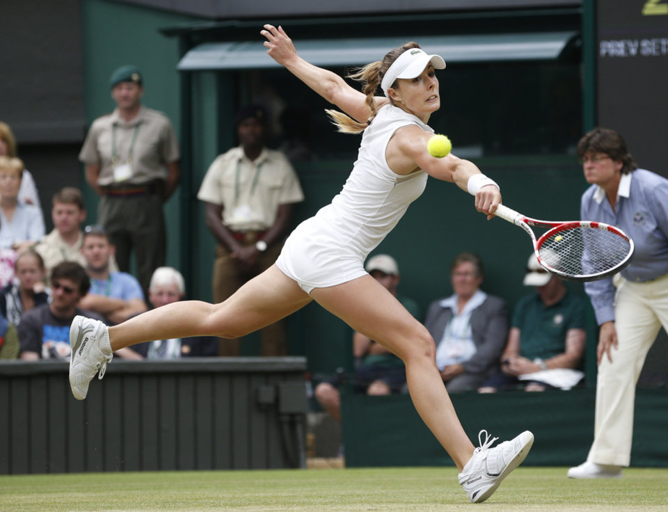 Photo - Alize Cornet of France plays a return to Eugenie Bouchard of Canada during their women's singles match at the All England Lawn Tennis Championships in Wimbledon, London, Monday, June 30, 2014. (AP Photo/Pavel Golovkin)