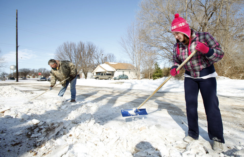 Photo - Dan Erwin and Miranda Stroud clear their driveway on E Harrison in Guthrie, February  3 , 2011. Photo by Steve Gooch, The Oklahoman