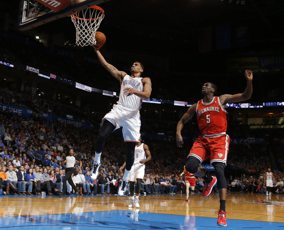 Oklahoma City\'s Thabo Sefolosha (25) goes past Milwaukee\'s Ekpe Udoh (5) during an NBA basketball game between the Oklahoma City Thunder and The Milwaukee Bucks at Chesapeake Energy Arena in Oklahoma City, Saturday, Jan. 11, 2014. Photo by Bryan Terry, The Oklahoman