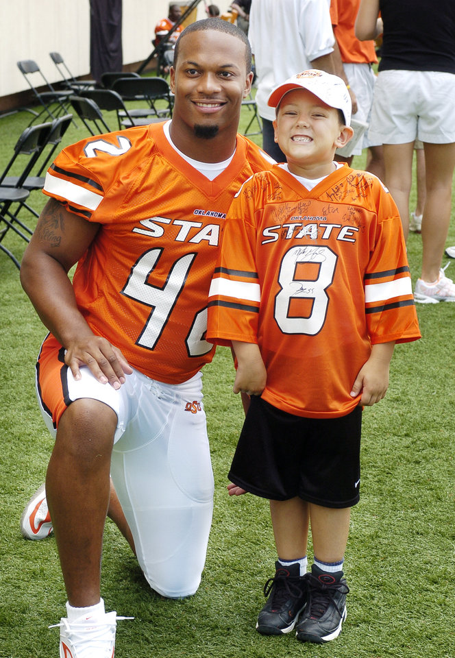 Photo -  STILLWATER, OK; TUESDAY, AUGUST 10, 2004; OSU media/fan apreciation day.   Tyler Kevin Norris, 6, from Stillwater, has a photo made with defensive lineman Trumain Carroll on the field.  Staff Photo by Steve Sisney