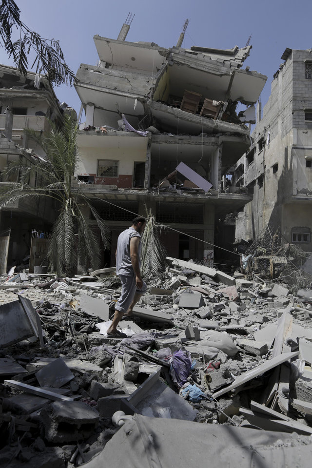 Photo - A Palestinian relative inspects the rubble of a three-story building belonging to the Abdul Hadi family after an Israeli strike in Gaza City in the northern Gaza Strip, Sunday, Aug. 24, 2014. (AP Photo/Adel Hana)