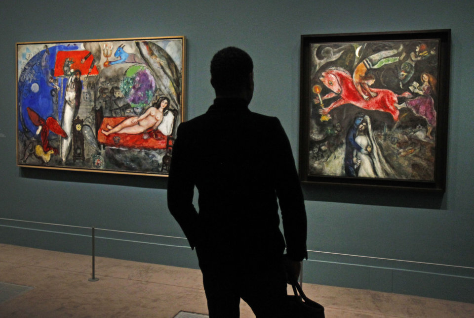 Photo - A member of the media views a painting by Russian artist Marc Chagall before the opening of the exhibition: Chagall, between War and Peace, at the Luxembourg museum in Paris, Tuesday Feb. 19, 2013. The exhibition starts February 21 and ends July 21, 2013.  Painting at right is: 1944, Le  Cheval Rouge, and at left: 1944, A Ma Femme.(AP Photo/Remy de la Mauviniere)