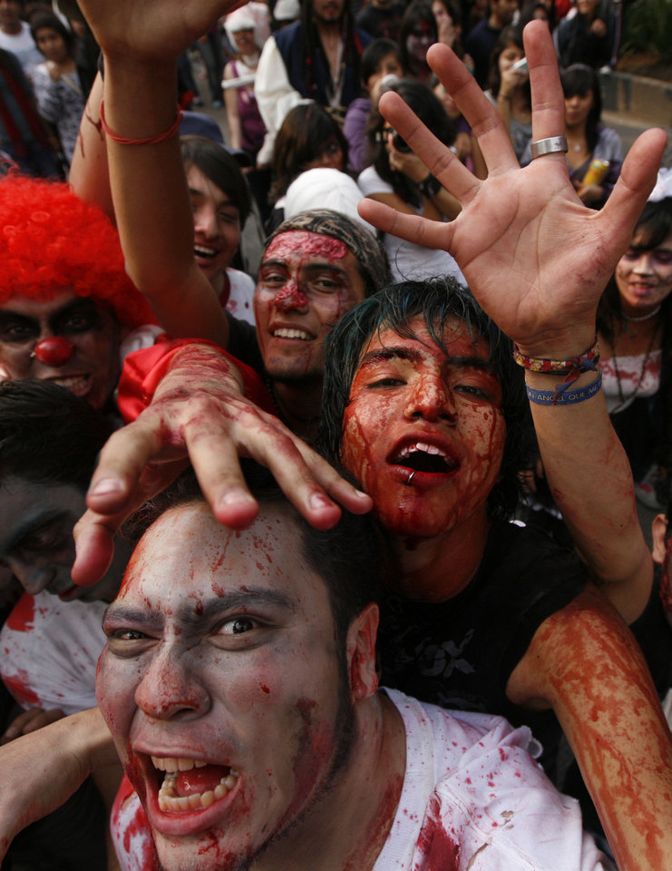 Photo - People dressed as zombies react to the camera during the V edition of the so-called 'Zombie Walk' in Mexico City, Saturday, Nov. 26, 2011. According to the organization 'Zombie Walk Mexico', the event gathered over 9,800 participants, breaking the previous record set in Asbury Park, in New Jersey in 2010 with 4,093 participants. Guinness World Records have not officially confirmed if Mexico holds the new record. (AP Photo/Marco Ugarte)