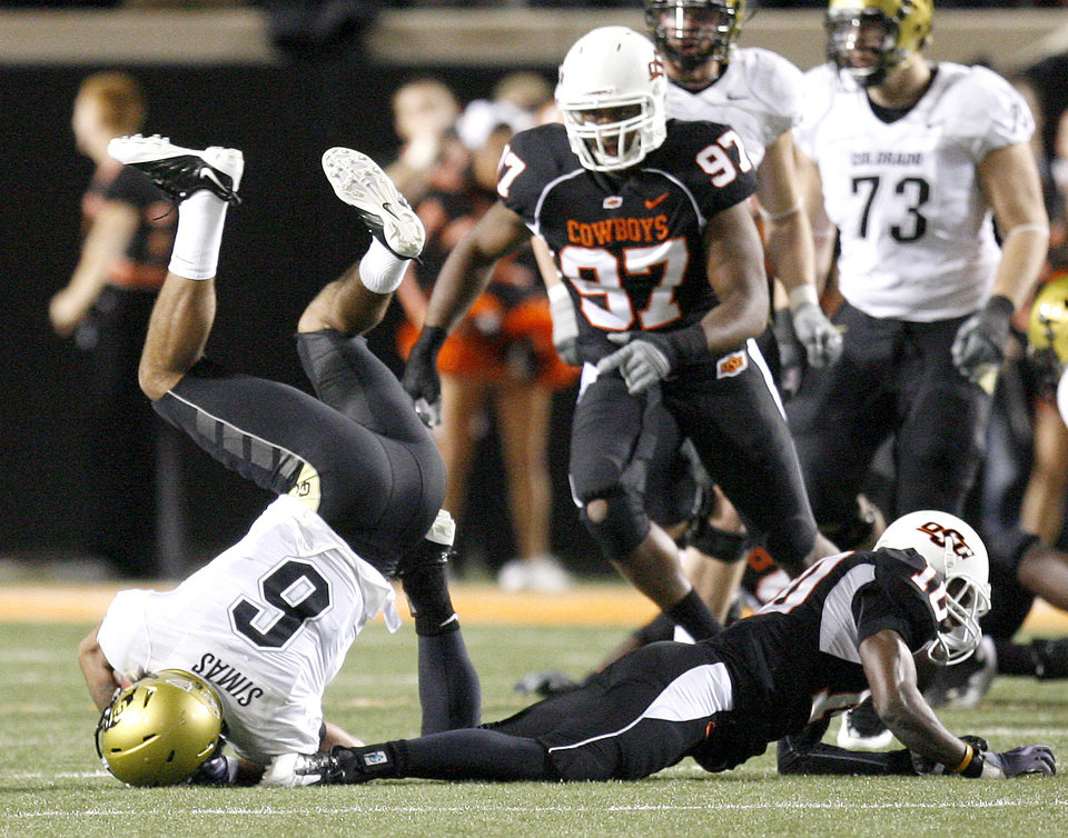 Photo - OSU's Markelle Martin brings down Colorado's Markques Simas during the college football game between Oklahoma State University (OSU) and the University of Colorado (CU) at Boone Pickens Stadium in Stillwater, Okla., Thursday, Nov. 19, 2009. Photo by Bryan Terry, The Oklahoman