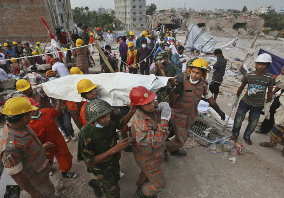 Photo - Bangladeshi rescue workers carry the body of a dead garment worker after it was retrieved from a building that collapsed on Wednesday in Savar, near Dhaka, Bangladesh, Sunday, April 28, 2013. Bangladesh rescuers on Sunday located nine people alive inside the rubble of the multi-story building, as authorities announced they will now use heavy equipment to drill a central hole from the top to look for survivors and dead bodies. (AP Photo/Kevin Frayer)