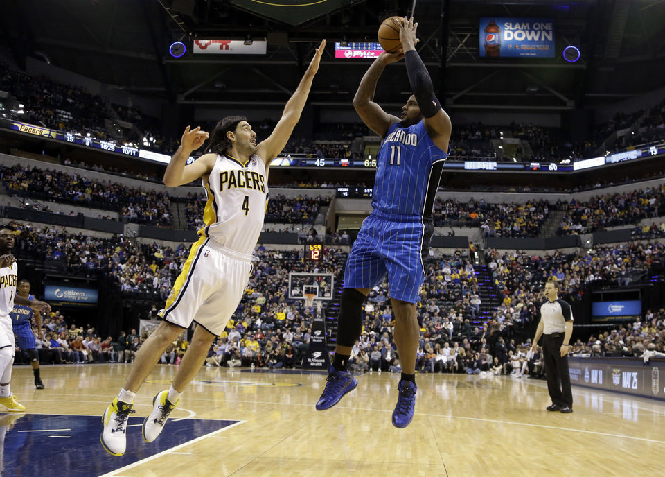 Photo - Orlando Magic forward Glen Davis, right, pulls up for a shot over Indiana Pacers forward Luis Scola in the first half of an NBA basketball game in Indianapolis, Monday, Feb. 3, 2014. (AP Photo/Michael Conroy)