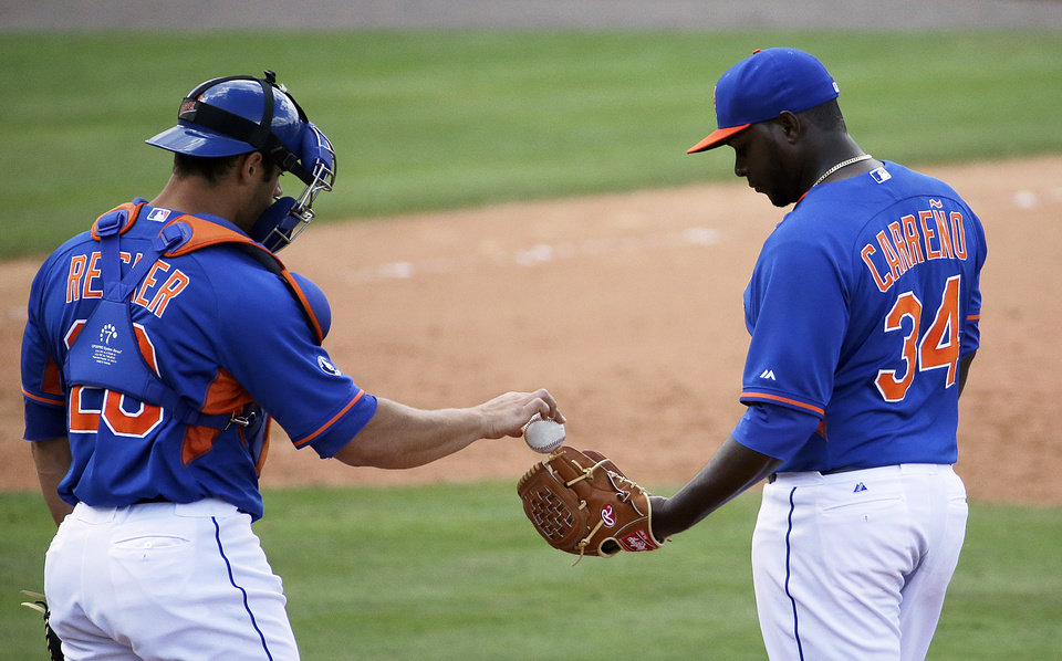 Photo - New York Mets relief pitcher Joel Carreno, right, is handed the ball by catcher Anthony Recker after Carreno walked St. Louis Cardinals' Stephen Piscotty to score teammate Scott Moore in the eighth inning of an exhibition spring training baseball game, Wednesday, March 12, 2014, in Port St. Lucie, Fla. (AP Photo/David Goldman)