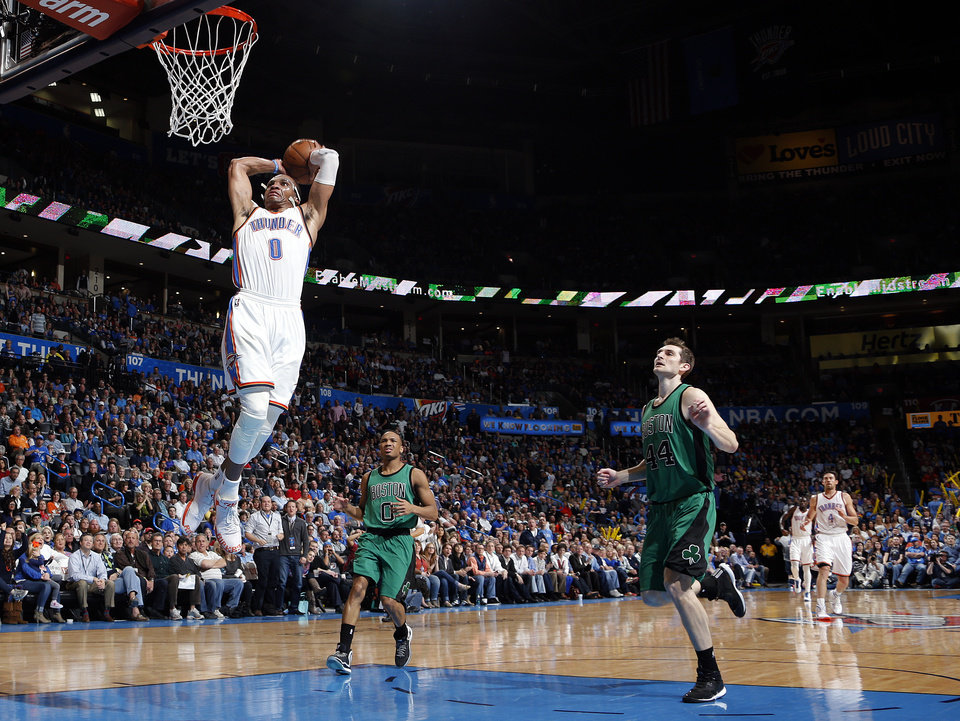 Photo - Oklahoma City's Russell Westbrook (0) goes up for a dunk in front of Boston's Avery Bradley (0) and Tyler Zeller (44) during the NBA basketball game between the Oklahoma City Thunder and the Boston Celtics at the Chesapeake Energy Arena in Oklahoma City, Wednesday, March 18, 2015. Photo by Sarah Phipps, The Oklahoman