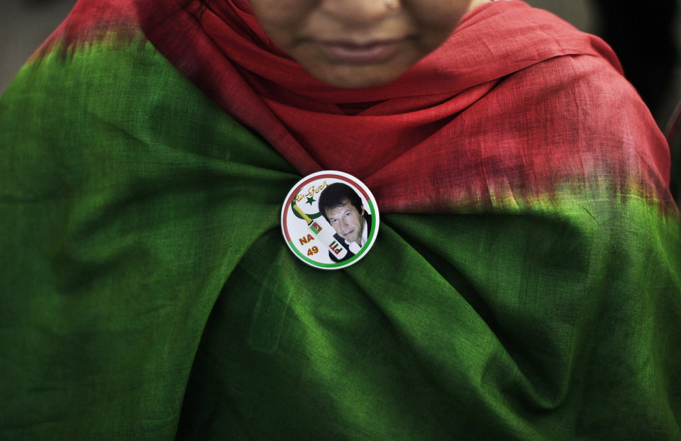 Photo - A Pakistani supporter of former cricket star-turned-politician, and leader of Pakistan Tehreek-e-Insaf party, Imran Khan, wearing a pin bearing Khan's image, takes part during a rally in Islamabad, Pakistan, Thursday, May 9, 2013. Pakistan is scheduled to hold parliamentary elections on May 11, the first transition between democratically elected governments in a country that has experienced three military coups and constant political instability since its creation in 1947. The parliament's ability to complete its five-year term has been hailed as a significant achievement. (AP Photo/Muhammed Muheisen)
