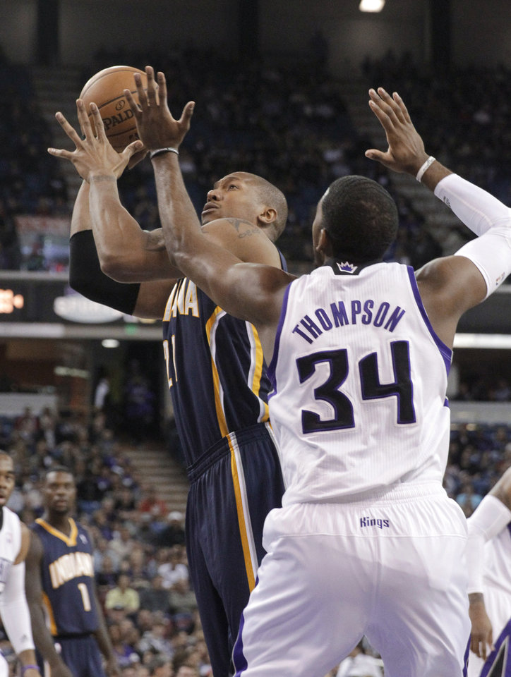 Photo - Indiana Pacers forward David West, left,  goes to the basket against Sacramento Kings forward Jason Thompson during the first quarter of an NBA basketball game in Sacramento, Calif., Friday, Jan. 24, 2014. (AP Photo/Rich Pedroncelli)