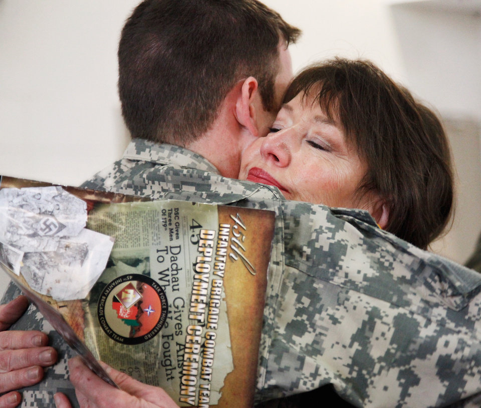 Photo - Sgt. Micah Bennett, Tulsa, gets a hug from his mother, Pamela Davis of Tulsa,  after the 45th Infantry Brigade Combat Team Deployment Ceremony in downtown Oklahoma City, Wednesday, Feb. 16, 2011. This will be Bennett's second deployment.  Photo by Jim Beckel, The Oklahoman