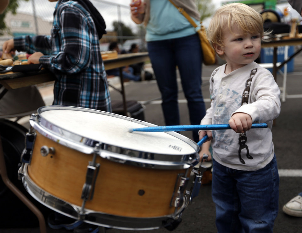 Photo - Conner Schwarz, 2, plays on a drum during the Norman Music Festival. Photo by Sarah Phipps, The Oklahoman  SARAH PHIPPS - SARAH PHIPPS