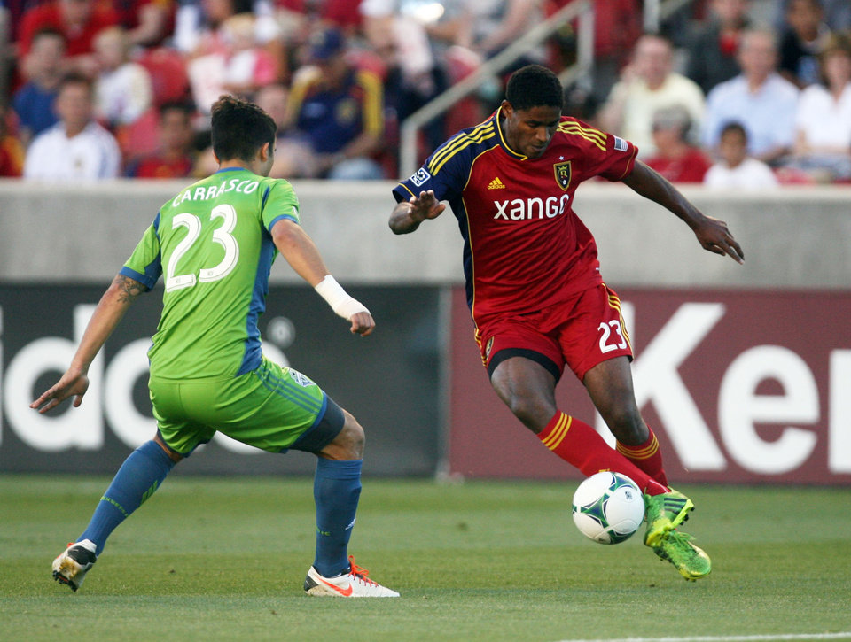 Photo - Real Salt Lake midfielder Khari Stephenson, right, tries to dribble past, left, Seattle Sounders FC midfielder Servando Carrasco (23) during the first half of an MLS soccer game at Rio Tinto Stadium in Sandy, Utah, on Saturday, June 22, 2013. (AP Photo/The Salt Lake Tribune, Kim Raff)  DESERET NEWS OUT; LOCAL TV OUT; MAGS OUT.