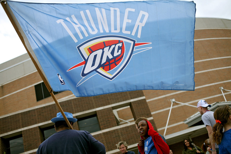 Photo - Carlos Garcia, of Oklahoma City, carries a flag as he joins fans outside the OKC Arena before the first round NBA Playoff basketball game between the Thunder and the Nuggets at OKC Arena in downtown Oklahoma City on Wednesday, April 20, 2011. Photo by John Clanton, The Oklahoman