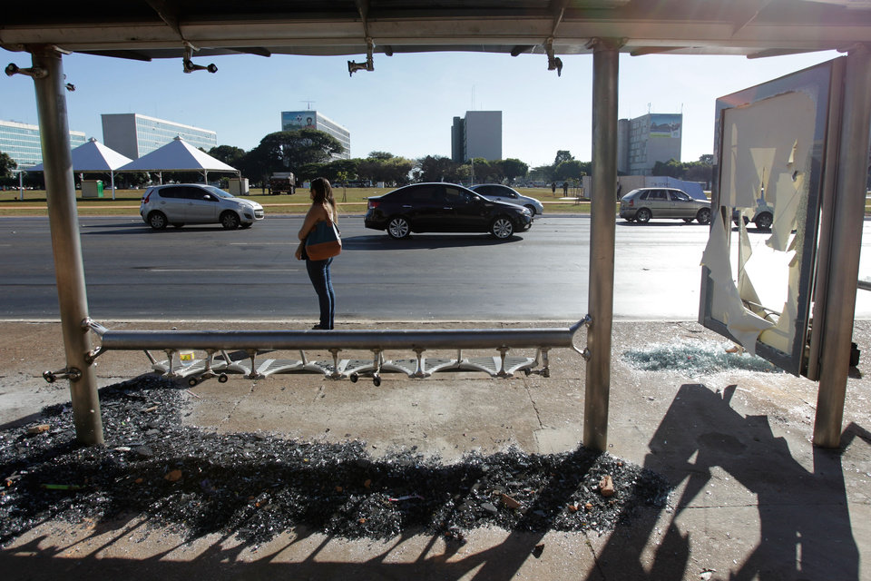Photo - A bus stop's window lays shattered below the seats after protests in Brasilia, the capital of Brazil, Friday, June 21, 2013. Police and protesters fought in the streets into the early hours Friday in the biggest demonstrations yet against a government viewed as corrupt at all levels and unresponsive to its people. (AP Photo/Eraldo Peres)