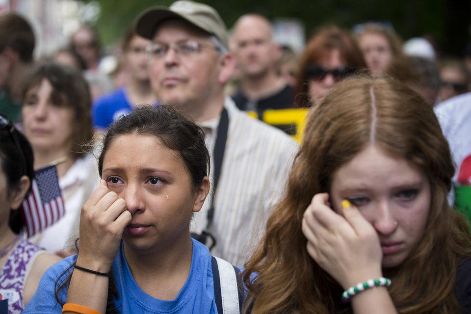 Photo - Michelle Zarisis, of Newtown, Conn., wipes away a tear at a rally outside city hall to call for tougher gun control laws, Saturday, June 14, 2014, in New York. The protest was underwritten by former New York Mayor Michael Bloomberg, one of the most visible gun control advocates in the U.S., and included relatives of some of those slain in the 2012 shooting rampage at Sandy Hook Elementary School. (AP Photo/John Minchillo)