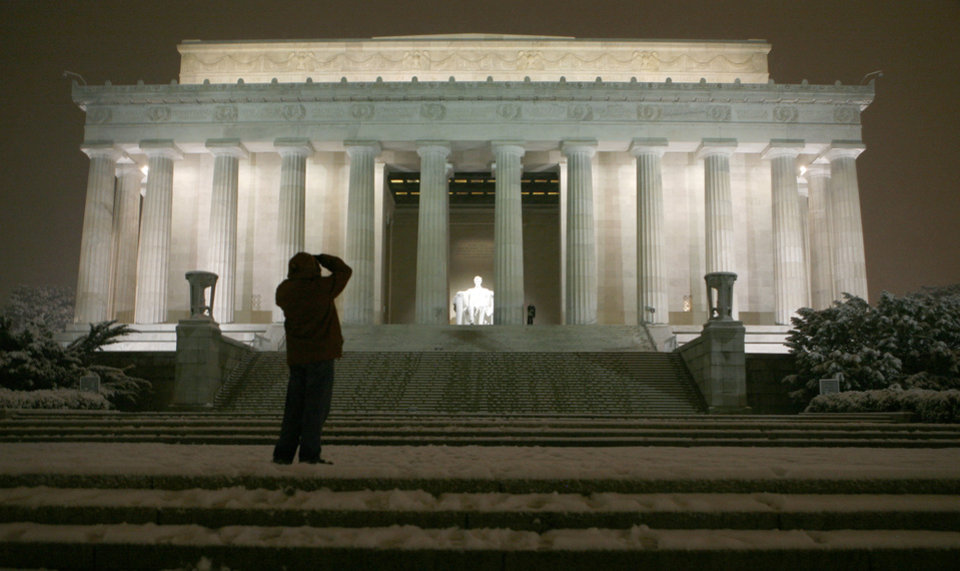 A tourist stops to take a picture of the snow dusted Lincoln Memorial during a winter storm late Wednesday, Dec. 5, 2007 in Washington. (AP Photo/J. David Ake)