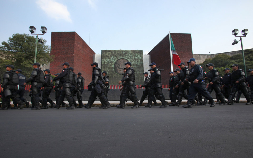 Photo - Riot police take position Wednesday outside the National Congress during a protest against the newly approved energy reform bill in Mexico City. AP Photo  Marco Ugarte