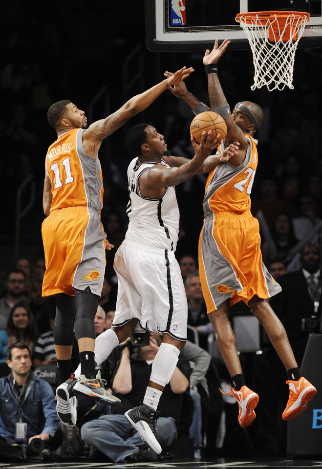 Photo - Brooklyn Nets' Andray Blatche (0) shoots between Phoenix Suns' Markieff Morris (11) and Jermaine O'Neal (20) in the second half of an NBA basketball game on Friday, Jan., 11, 2013 at Barclays Center in New York. The Nets won 99-79. (AP Photo/Kathy Kmonicek)