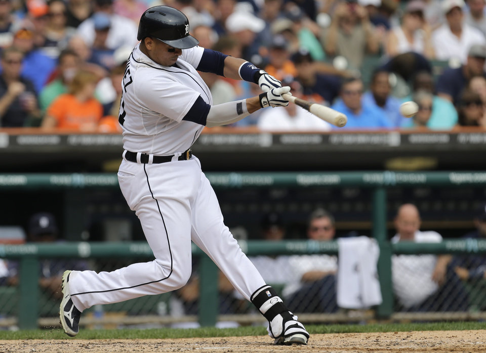 Photo - Detroit Tigers' Victor Martinez hits a one-run double against the Seattle Mariners in the seventh inning of a baseball game in Detroit, Thursday, Sept. 19, 2013.  (AP Photo/Paul Sancya)