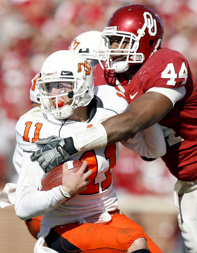 Photo - OSU's Zac Robinson (11) is tackled by Jeremy Beal (44) during the first half of the Bedlam college football game between the University of Oklahoma Sooners (OU) and the Oklahoma State University Cowboys (OSU) at the Gaylord Family-Oklahoma Memorial Stadium on Saturday, Nov. 28, 2009, in Norman, Okla. Photo by Sarah Phipps, The Oklahoman