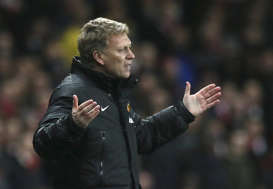 Photo - FILE - In this Wednesday, Feb. 12, 2014 file photo Manchester United's manager David Moyes gestures to his team during their English Premier League soccer match between Arsenal and Manchester United at the Emirates stadium in London. Manchester United says manager David Moyes has left the Premier League club after less than a year in charge, amid heavy speculation he was about to be fired. United released a brief statement in its website Tuesday, saying the club