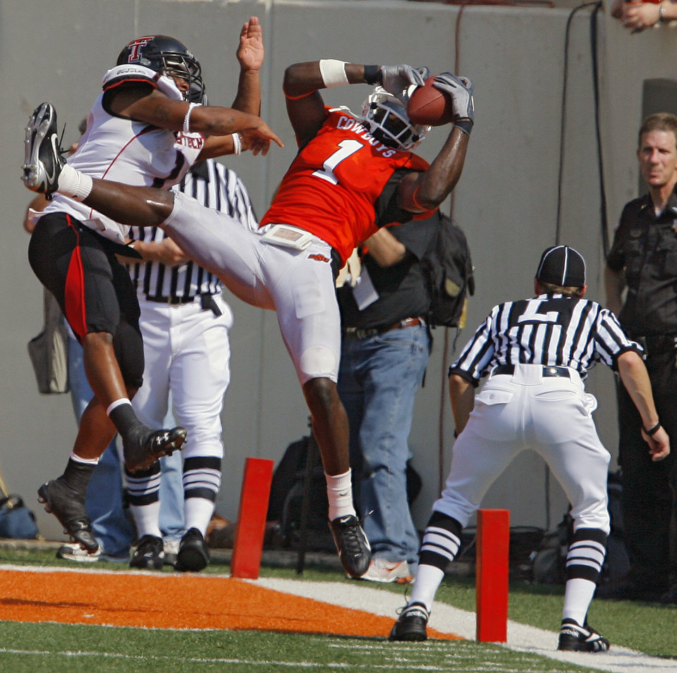 Photo - Oklahoma State's Dez Bryant (1) pulls in a touchdown pass in front of Texas Tech's Marcus Bunton (1) during the first half of the college football game between the Oklahoma State University Cowboys (OSU) and the Texas Tech University Red Raiders (TTU) at Boone Pickens Stadium  on Saturday, Sept. 22, 2007, in Stillwater, Okla. 