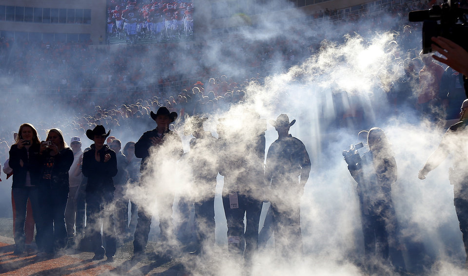 Smoke filters through the crowd as the OSU team takes the field before a college football game between Oklahoma State University (OSU) and Texas Tech University (TTU) at Boone Pickens Stadium in Stillwater, Okla., Saturday, Nov. 17, 2012.  Photo by Bryan Terry, The Oklahoman